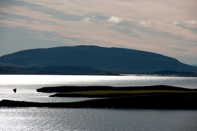 遠くの山と前景の島の湖で揺れる日の出