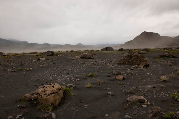 乾いた河川敷と砂塵の上昇による険しい山の風景