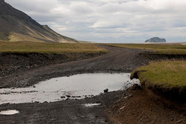 田園地帯と田舎道の汚れのある山と牧草地の景色