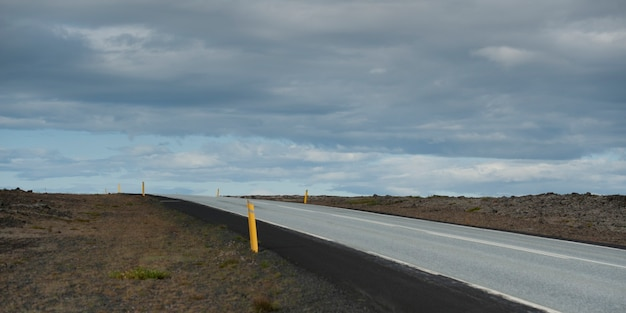 曇った空の下で地平線の上で消えている不毛のハイウェイ