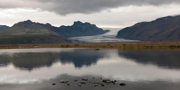 海岸線に沿って水に反射するヴァトナコク氷河、山脈、雲