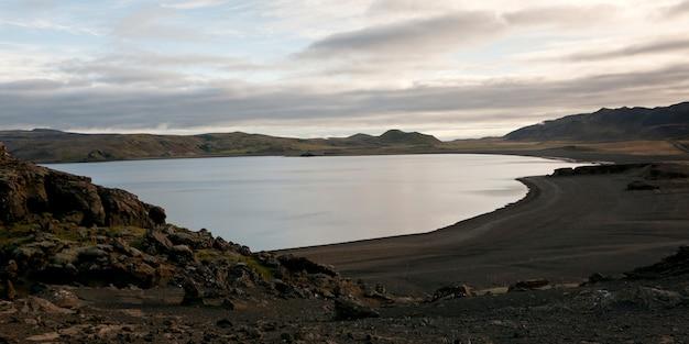 火山性の黒い砂と岩の丘がある穏やかな湖
