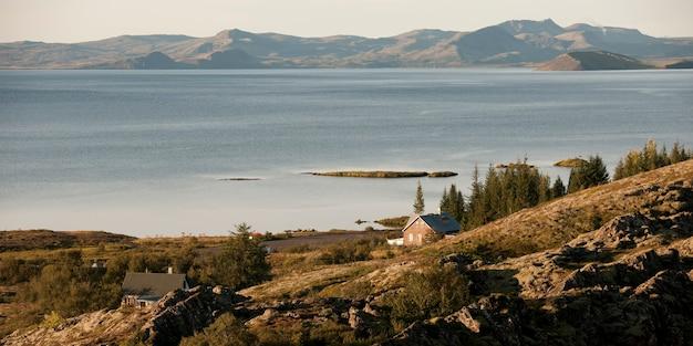 落ち着いた水の体と遠くの山々との険しい丘の上の住宅