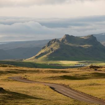 アイスランドの草原を通って山々に向かって消えていくハイウェー
