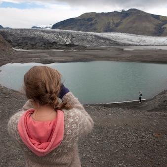 氷河の湖の写真を撮っている少女の写真館