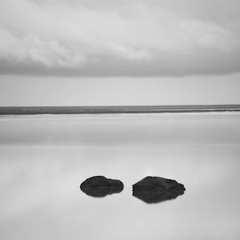 海岸近くの曇った空の下の落ち着いた湖の孤独な岩
