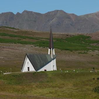 山の前の牧草地の丘の後ろに隠されている農村教会