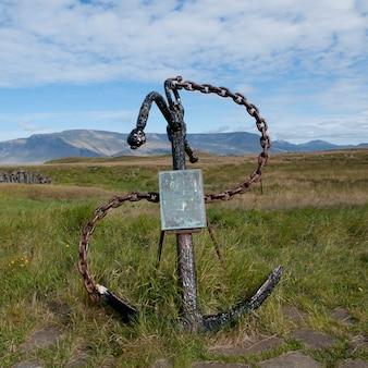 船のアンカーと溶接された鎖は山の前のフィールドの道標として