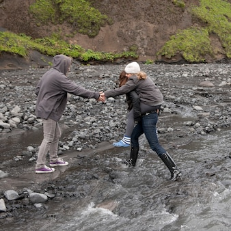 川のほとりを歩いて岩場の川沿いの峡谷を歩く人々