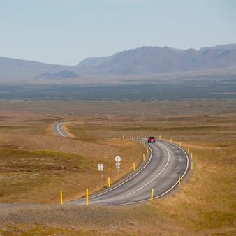 遠くの山々に向かって田舎を蛇行するハイウェイの車