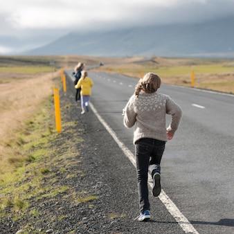 田舎の高速道路のそばを走っている女の子たち