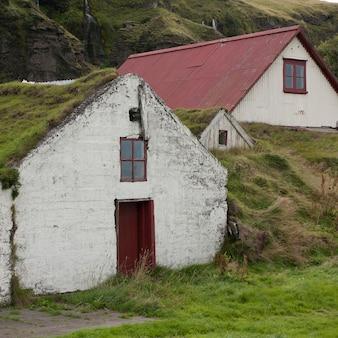 丘陵地に埋葬され、草で覆われた農村の農場の建物