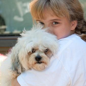 森の湖、オンタリオ州で彼女の犬を抱擁する若い女の子
