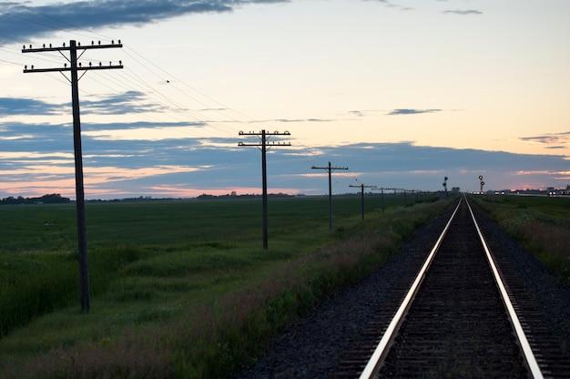 レイクオブザウッズ、オンタリオ州の夕暮れの空に対する鉄道路線と水柱