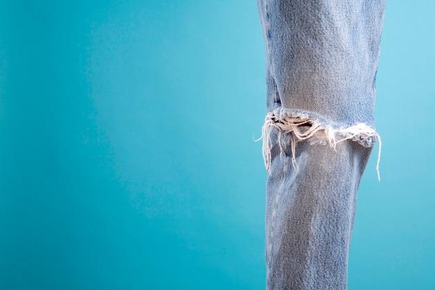 Одна изношенная джинсовая нога