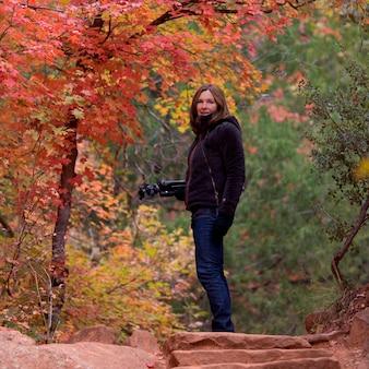 アメリカ、ユタ州、シオン国立公園の森林で三脚で立っている女性