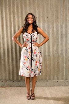 コンクリートの壁の前に立つ若いアフリカ系アメリカ人の肖像画とカメラで笑顔の肖像