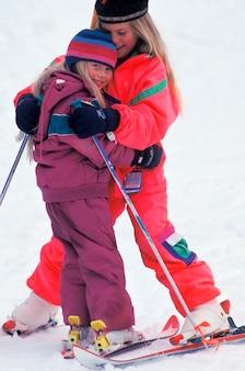 Сестры обнимаются на лыжной горе