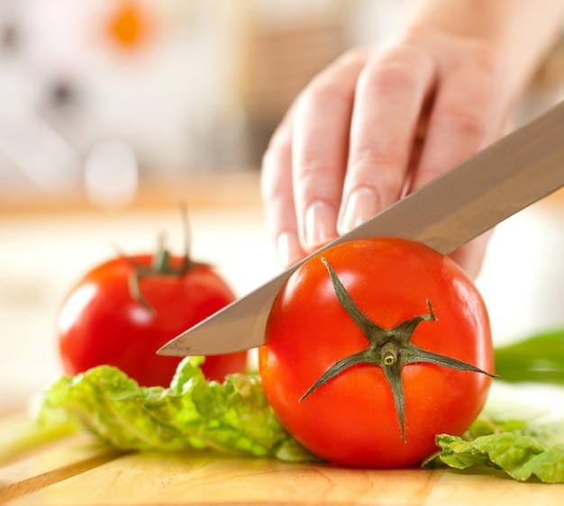 新鮮な野菜の後ろにトマトを切る女性の手。