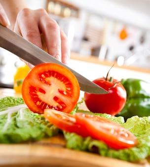 Руки женщины резки помидор, за свежие овощи.