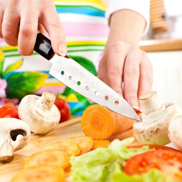 Руки женщины резки морковь, за свежие овощи.