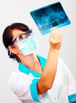 Женщина-врач с рентген челюсти