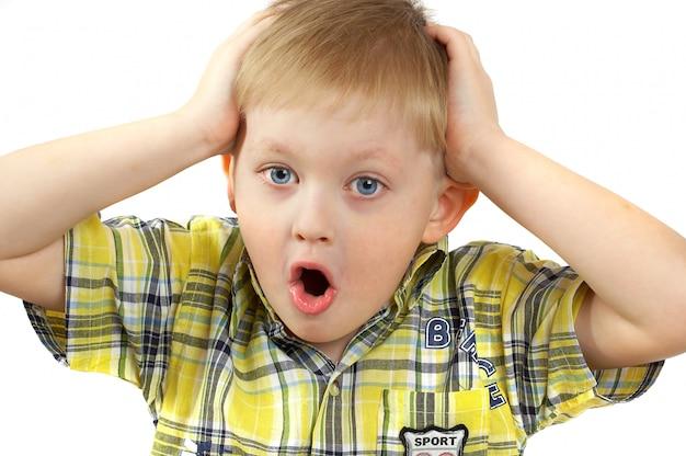Блондинка красивый мальчик удивлен, руки на голову