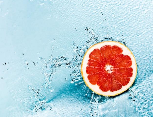 赤いグレープフルーツの新鮮な水のしぶき