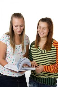 Две девочки-подростки улыбаются и читают книгу, изолированные на белом