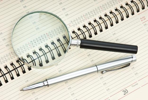Ручка и увеличительное стекло на календаре
