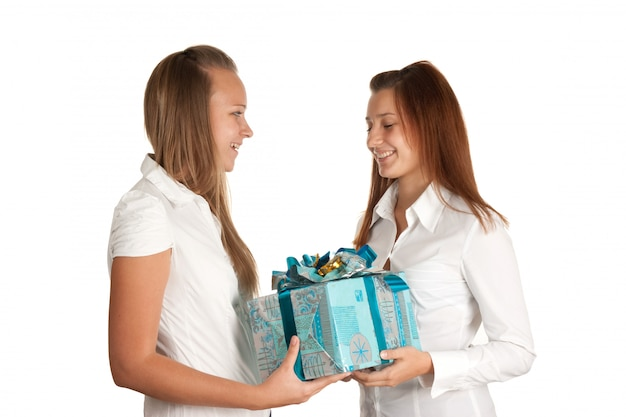 Молодые девушки и коробка с подарком на белом фоне