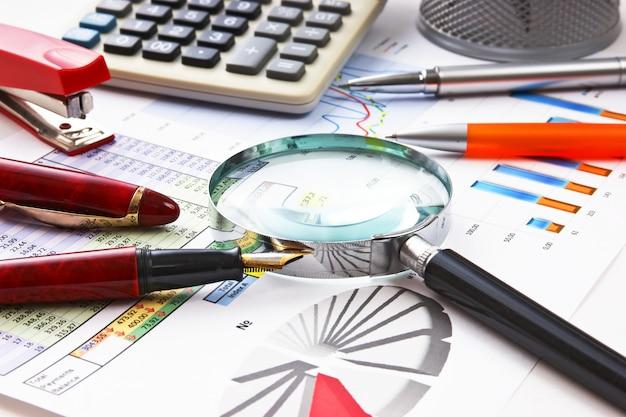Ручка, увеличительное стекло и рабочий документ с диаграммой