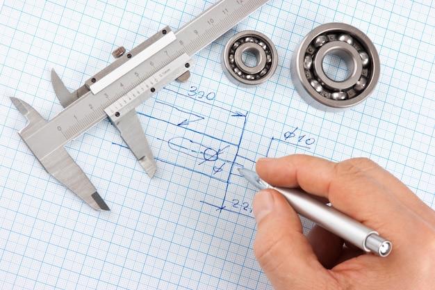 Перо в руке и технический рисунок на миллиметровой бумаге