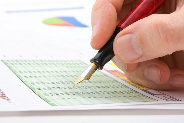 男性の手はテーブルの上に横たわるビジネス文書で書いています