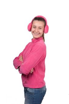 白で隔離されるピンクのヘッドフォンで幸せな女の子ティーン