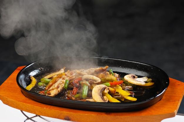 Мясо на гриле с грибами и овощами в сковороде