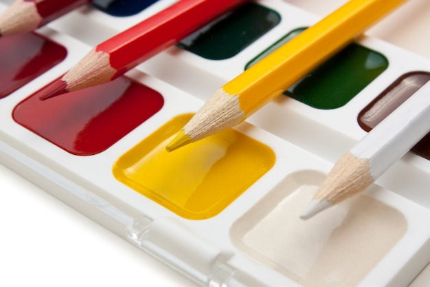 Цветные карандаши и акварельные краски, изолированные