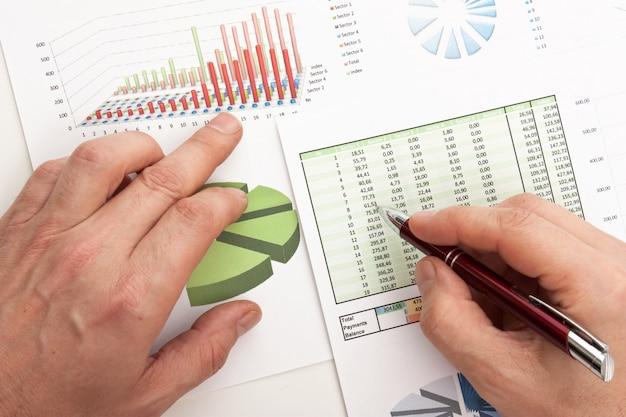 Мужская рука пишет в деловой документ, лежащий на столе