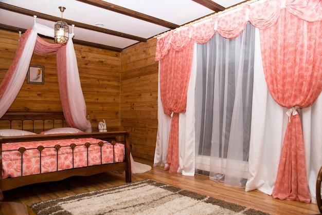 コテージのインテリア:ベッドとカーテン付きの窓