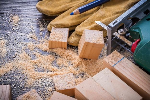 Карандаш электрический лобовые опилки работает защитные перчатки и деревянные доски на старинных фоне дерева концепции строительства