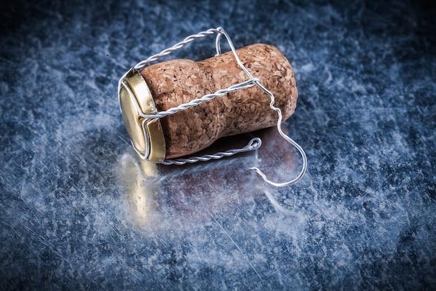 Шампанское пробки витой проволоки на поцарапанной металлической предпосылке концепции спирта