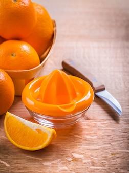 木製の机の上のオレンジとフルーツナイフのスクイーザ