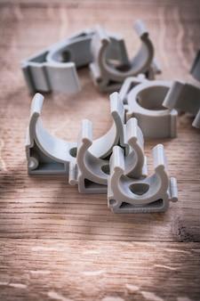 Пластмассовые фиксаторы для водопроводных труб на деревянной доске концепции строительства