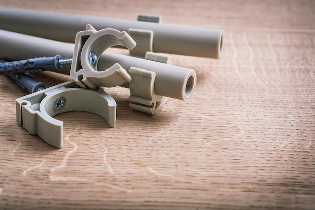 木の板にクリップが付いているポリプロピレンの固定具そして管