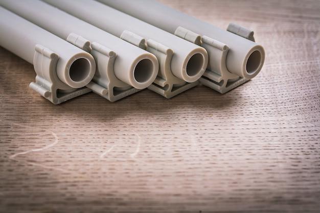 木の板のクリップ付きポリプロピレンパイプ