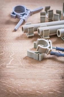 ポリプロピレン固定具と木製ボード上のクリップ付きパイプのセット