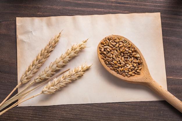 Колосья пшеницы и деревянная ложка с зернами на винтажной бумаге