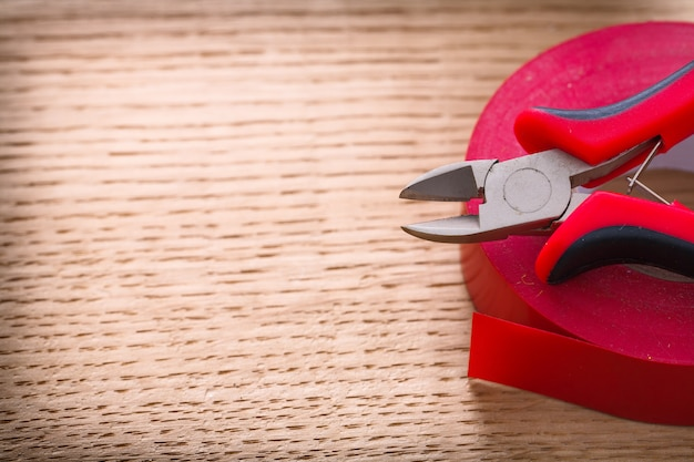 赤いニッパーと木の板に絶縁テープ