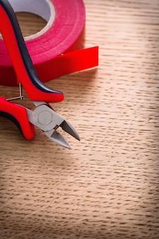 垂直ビュー赤いニッパーと木の板に絶縁テープ