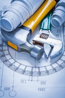 調整可能なスパナは建設計画とクローハンマーの建物の概念を重ね